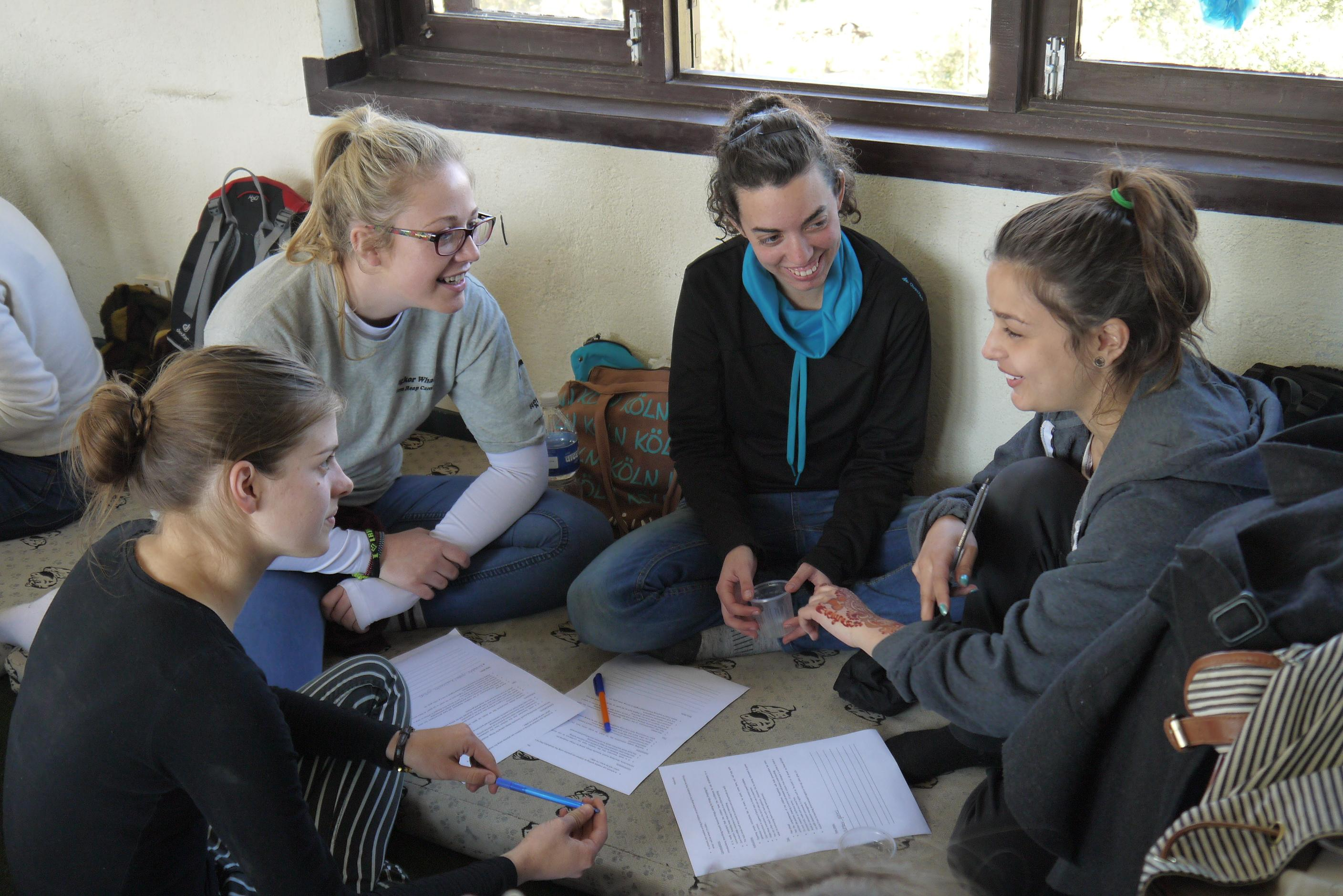 Projects Abroad female Care HIV/Aids volunteers working in Nepal prepare an educational activity.